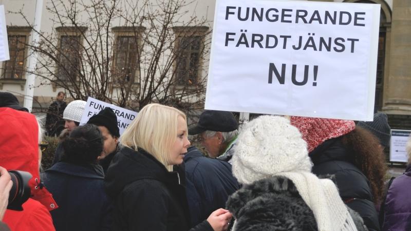 """Folksamling framför landstingshuset och plakat med texten """"Funderande färdtjänst NU!"""""""