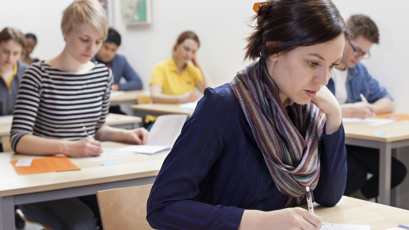 Människor som sitter i en sal och skriver prov. Fotograf: Erik Lundback.
