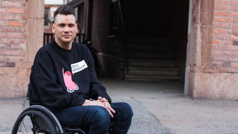 Anders Westgerd sitter i en rullstol framför en tegelvägg.