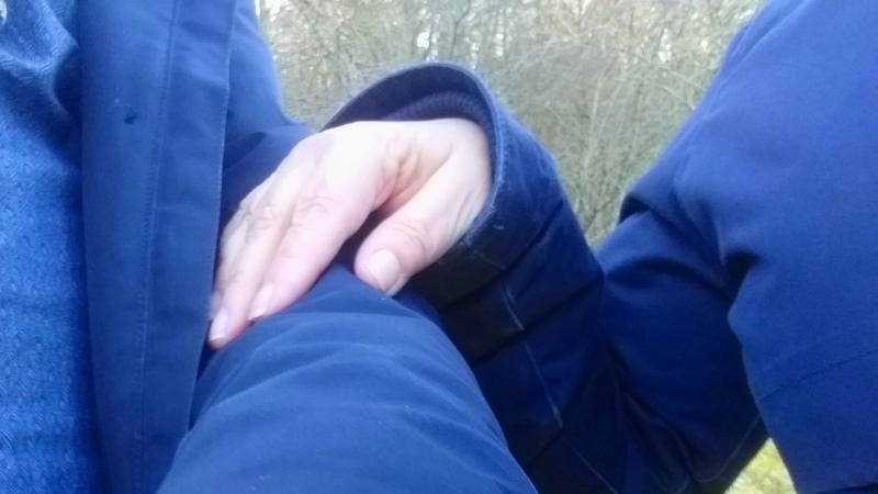 En hand som håller på en arm.