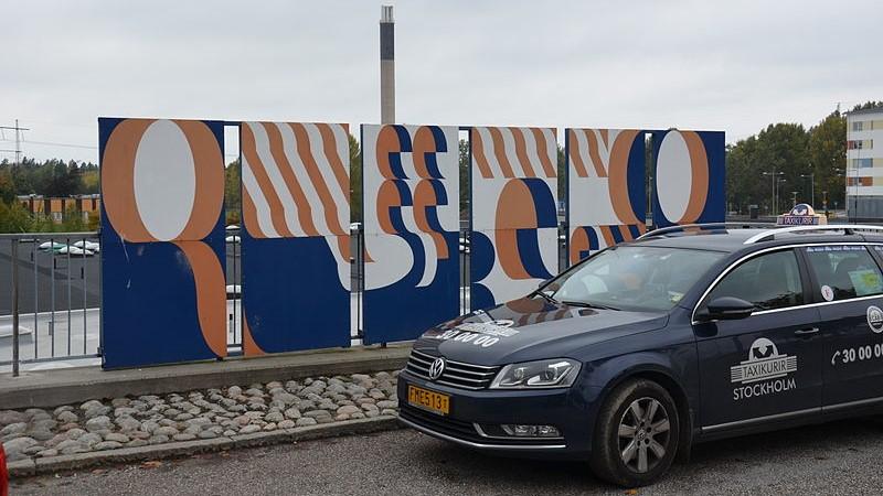 """En taxibil står till höger i bild framför konstverket """"Hej patient"""" vid entrén till Huddige sjukhus. Verket består av paneler med blått, vitt och aprikosfärgade former på."""
