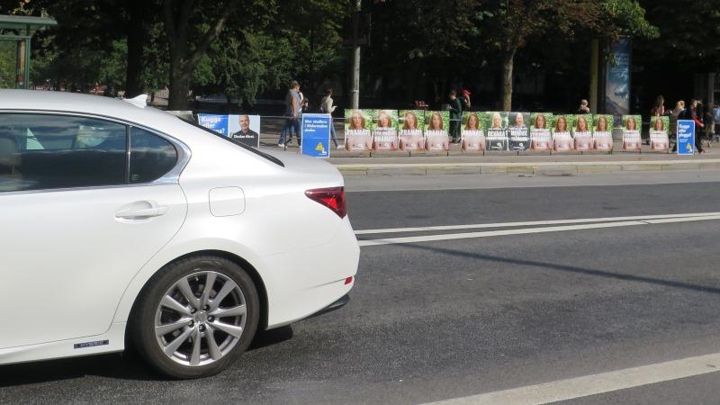 Ett tjugotal valaffischer på rad på ett staket som löper längs en gata. Bakre delen av en bil i bildens vänsterkant.
