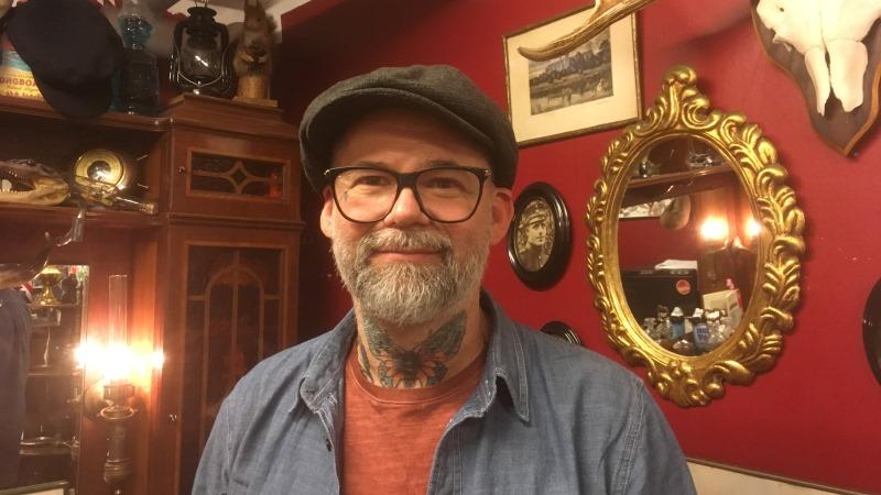 Man med grått helskägg, en stor fjärilstatuering på halsen och glasögon, klädd i keps. I bakgrunden en röd vägg med tavlor och spegel med tjock guldram.