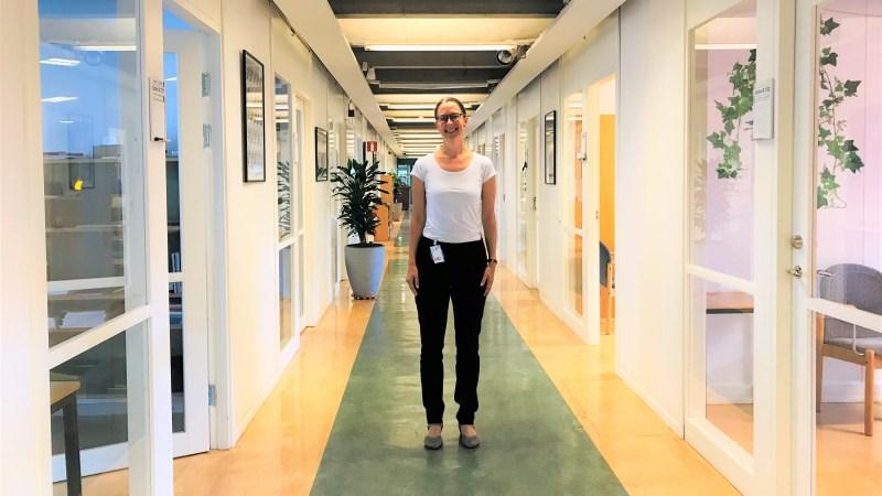 Leende kvinna med mörkt hår i tofs och mörka glasögon, klädd i vit tröja och svarta byxor, står i en lång ljus korridor med glasdörrar och fönster till kontor.