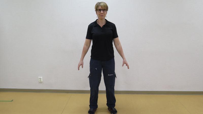Kortklippt kvinna med glasögon i mörka kläder står med benen en bit isär och armarna sträckta ut från kroppen.