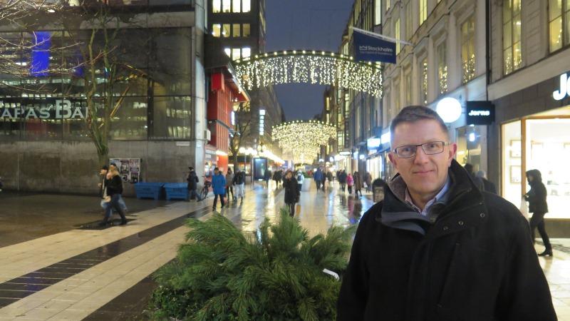 Man med glasögon och mörk jacka framför julbelysning på Drottninggatan, som pryds av bågformade ställningar med hängande lodräta ljusslingor med varmt sken var tionde meter från Sergels torg hela vägen till Riksbron