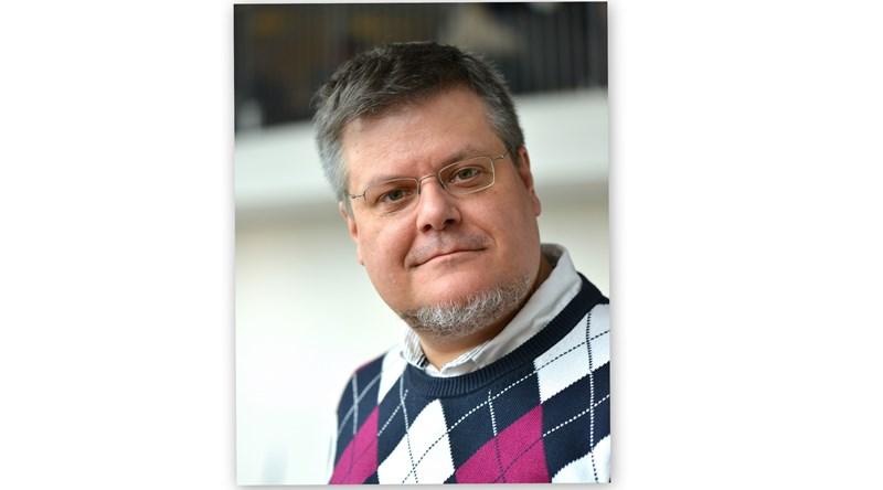 Närbild på medelåldersman med kort grått hår och blåröd rutig tröja