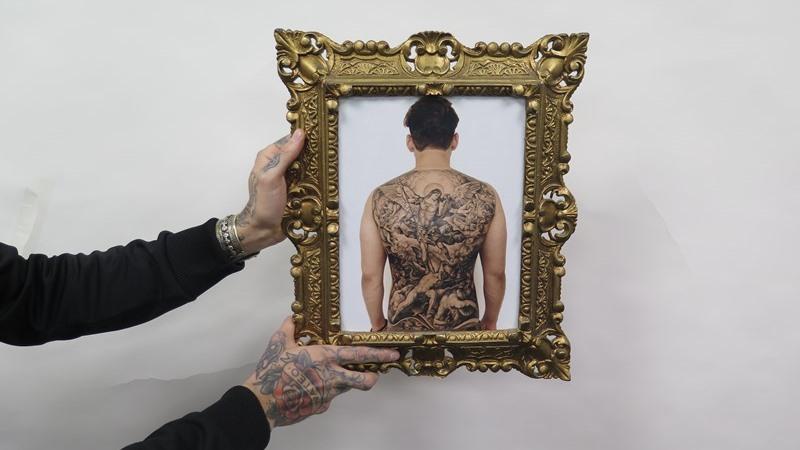 Två tatuerade händer håller mot vit bakgrund fram en guldram med foto av en heltatuerad rygg.
