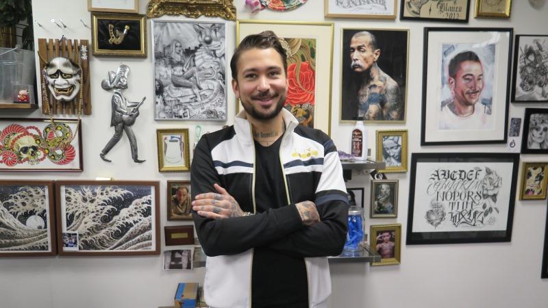 En leende man med mörkt kort hår, bruna ögon och kort helskägg står med armarna i kors framför en vägg fullhängd med foton på tatueringar.