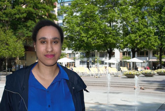 Aniké Kadiri är en av en handfull svenskar på utbildningen. Här syns hon iförd marinblå blus och mörkblå jacka. Hon har mörkt hår som är uppsatt. I Bakgrunden syns en fontän och grönska.