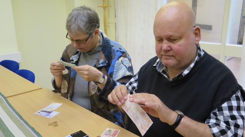 Anita Maddock och Rolf Eriksson testar mynt och sedlar.