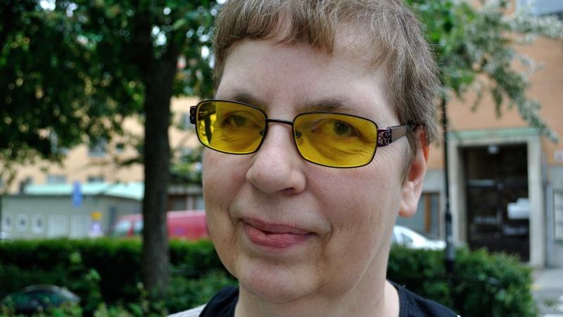 Anita Maddock har kort brunt hår och orangea glasögon.