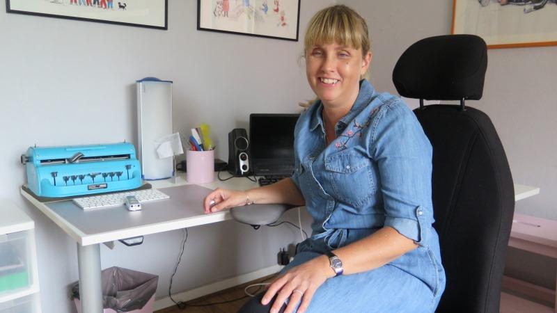 Leende blond kvinna med lugg och tofs i nacken, klädd i jeansklänning i kontorsmiljö.