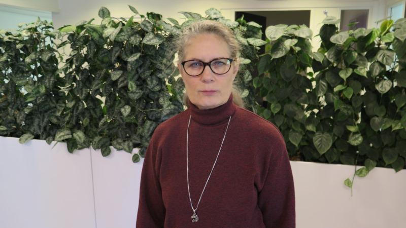 Kvinna med grått hår i tofs och glasögon, klädd i vinröd polotröja framför gröna växter i kontorslandskap.
