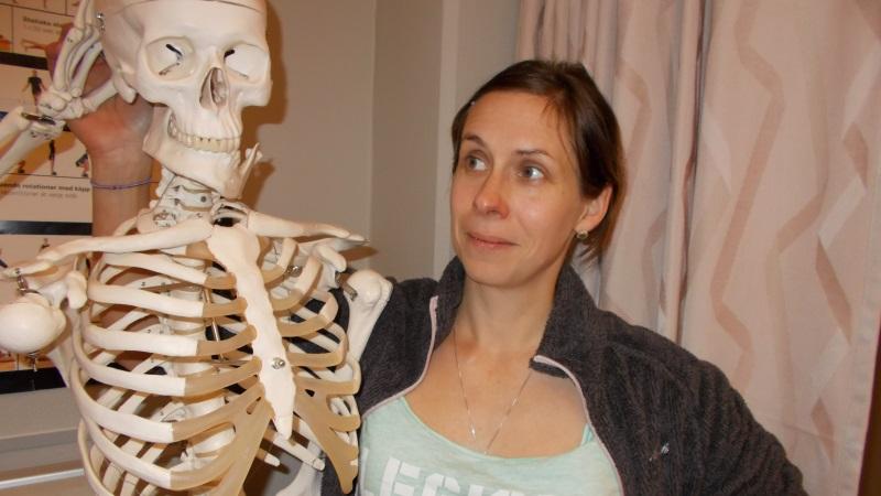 Kvinna med brunt hår invid ett skelett som gör honör.