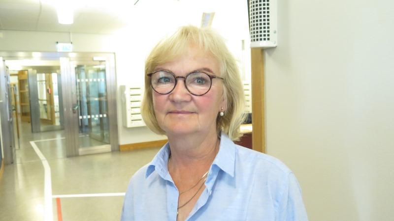 Kvinna med glasögon och kort, blont hår klädd i ljusblå skjorta.