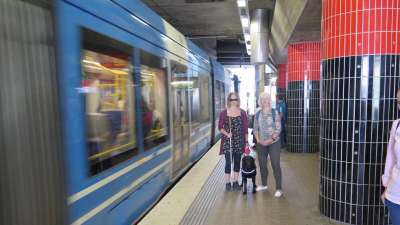 En kvinna med mörka glasögon, vit käpp och ledarhund vid sin sida står intill en blond, korthårig kvinna på en perrong medan ett tåg kommer körande till vänster i bild.
