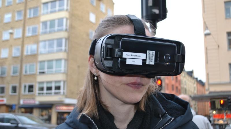 Rödblond kvinna i närbild, hon har på sig ett par VR glasögon, stadsbild.