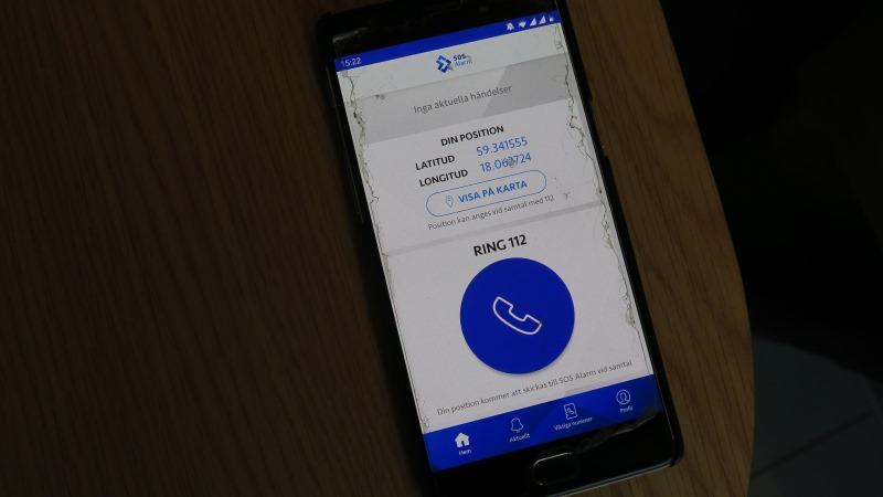 En mobil i närbild på ett brunt bord. SOS appens sida är uppe, den har vit bakgrund och i nedre delen av den en stor rund blå cirkel med en vit grafisk telefonlur i. Ovanför står ring 112. Ikonen trycker man på för att ringa.