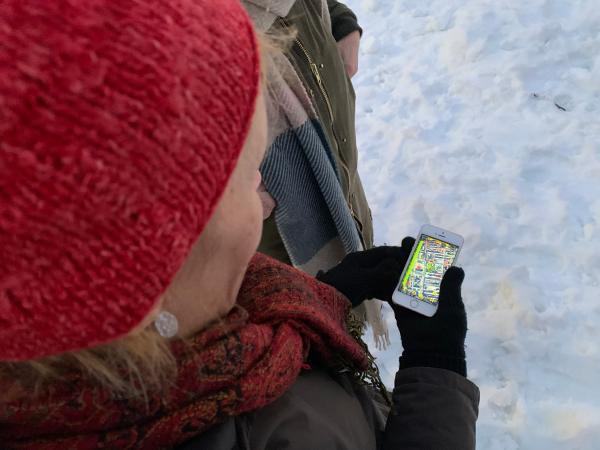 Ett foto uppifrån visar en person i en röd mössa till vänster i bild som tittar ner på en mobiltelefon med en karta i displayen. Marken är täckt av snö till höger i bild.