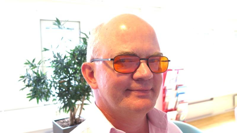 Tunnhårig man med glasögon med orangetonade glas.