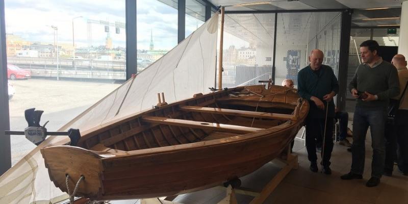 Till höger i bild står en grupp människor intill en träbåt som finns mitt i bild. Bakom båten till vänster ligger ett hissat segel framför ett stort ljust fönster.