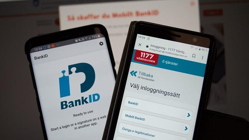 Två mobiltelefoner bredvid varandra. På skärmen till vänster visas loggan för BankID. Skärmen till höger visar 1177 Vårdguiden inloggning till e-tjänster. I bakgrunden skymtar en suddig text på en datorskärm: Så skaffar du BankID.