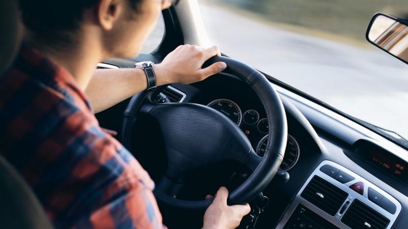 Bilinteriör med en man som håller händerna på ratten.