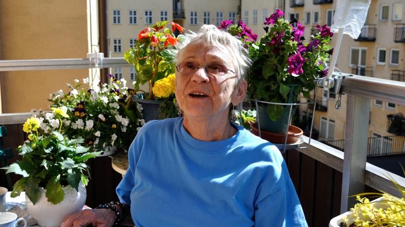 Barbro Lindell har kort grått hår, glasögon och en blå tröja. Hon är omgiven av blommarna på sin balkong.