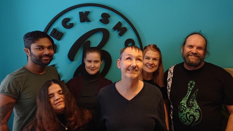 En grupp på sex leende personer står samlade framför en turkos vägg med en logotyp där ett B och ordet Becksmo är skrivna.