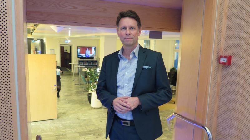 Medelålders man med mörkt hår, klädd i mörkblågrå kostym och ljusblå skjorta. I bakgrunden skymtar receptionsmiljö med ståbord, TV och gröna växter.