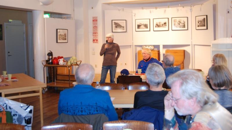 Birgit Holmgren till orda på Berättarcaféet. Kvinna med kort, grått hår och glasögon står med mikrofon i handen framför människor som sitter runt bord och fikar.