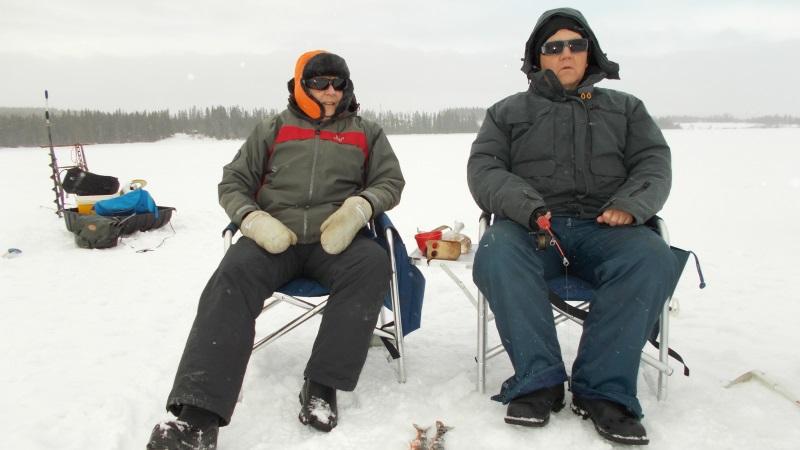 Två påpälsade fiskar i varsin stol med fiskespö, omgivna av vidsträckt snötäckt is.