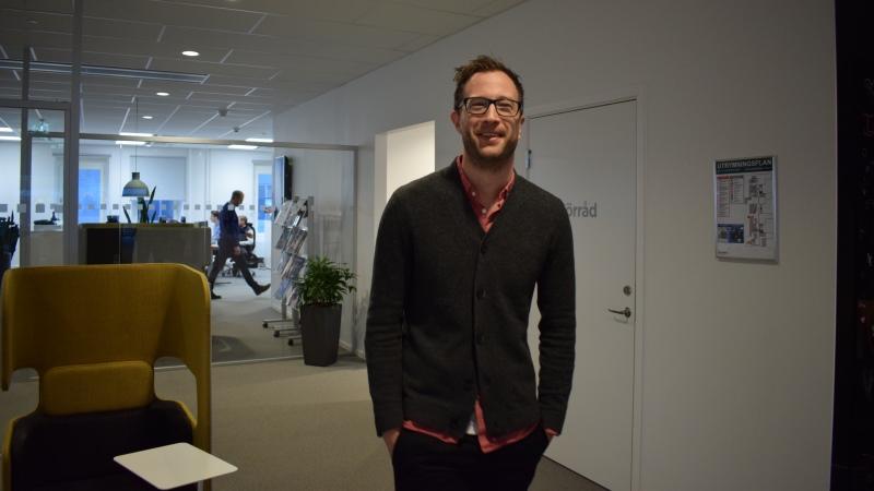 Brett leende man med fyrkantiga svarta glasögon, kort mörkt hår och kort skägg står med händerna i fickorna i kontorsmiljö.