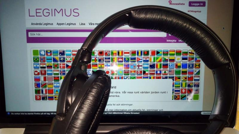 Stora hörlurar ligger framför en uppfälld laptop, där man skymtar Legimus webbplats.