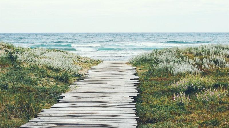 Brygga som leder ner till strand och hav