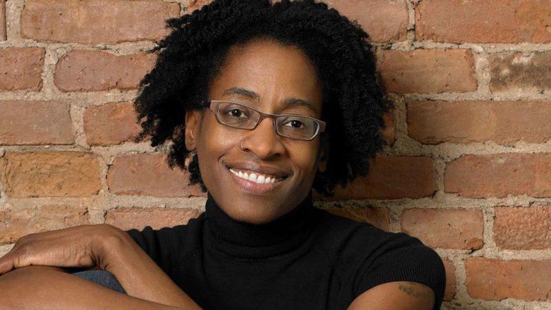 Ung svart kvinna med varmt och självsäkert leende.