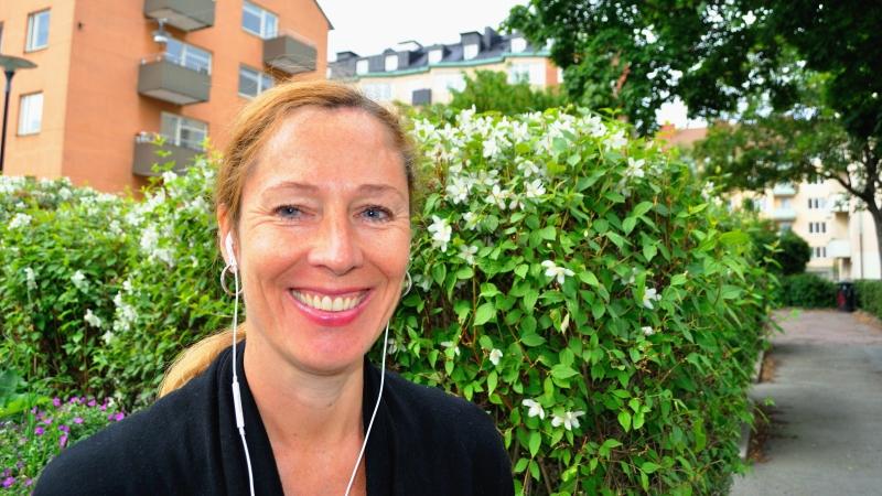 Leende mellanblond kvinna med hörlurar i sommarmiljö