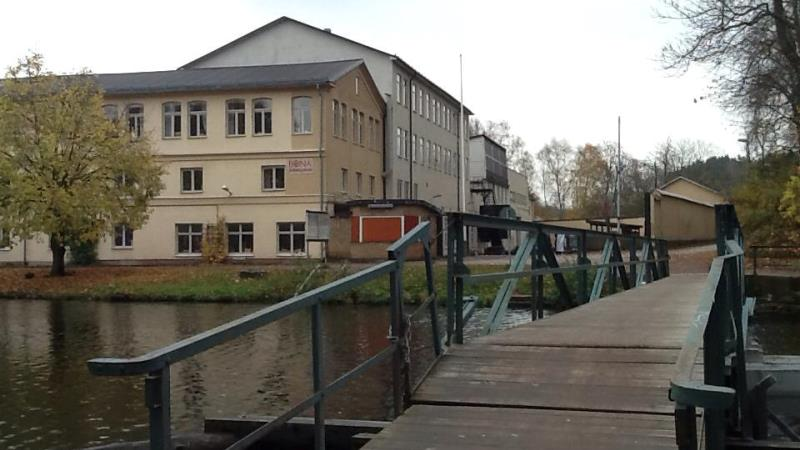 I förgrunden en träbro som leder över vatten till en ljusgul fyravåningsbyggnad till vänster i bild.