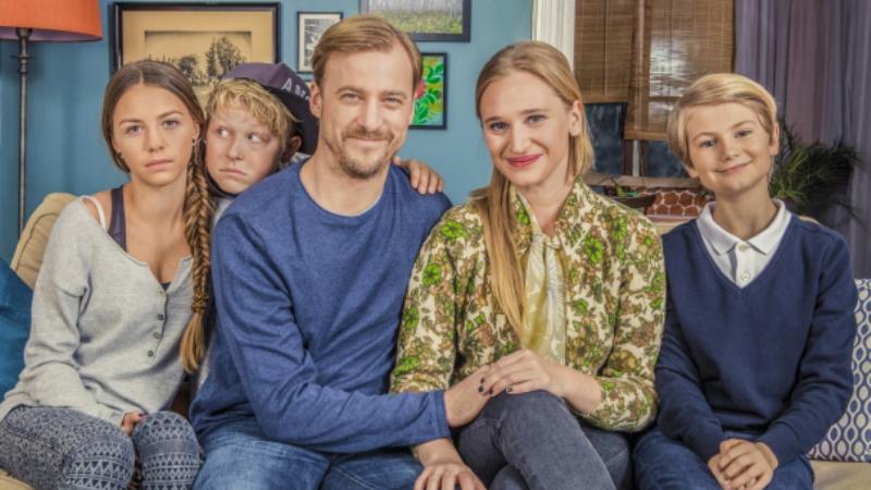 Bild på en familj med två glada föräldrar och tre barn. Ett av barnen ler brett, två av dem ser sura ut. Foto:SVT