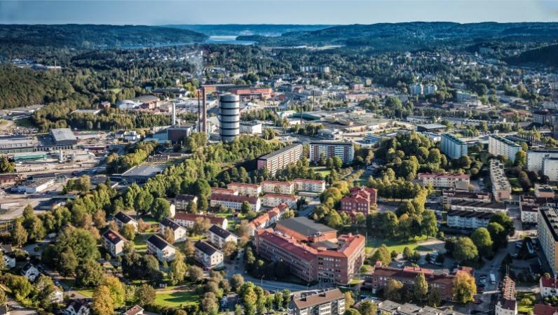 Flygfoto över en svenska stad med låga bostadshus, grönska och vatten som skymtar i översta kanten. Foto: Per Pixel Petersson.