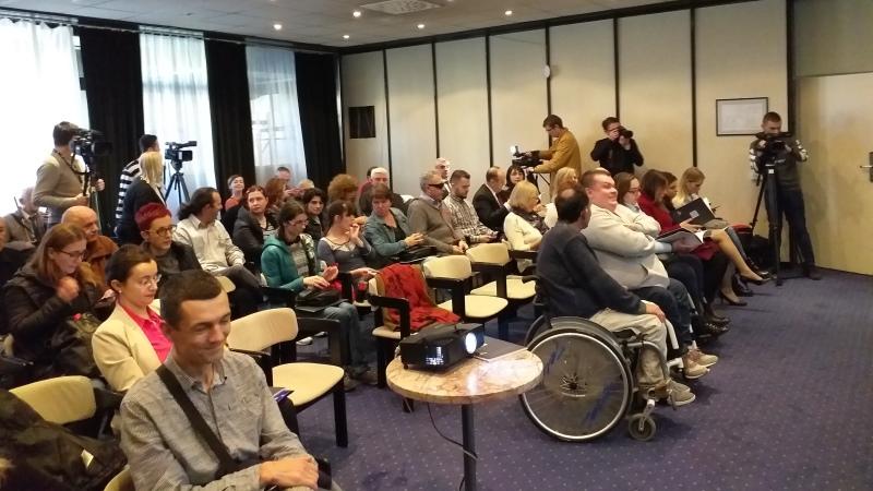 Flera vuxna personer sitter i en konferenssal och lyssnar.
