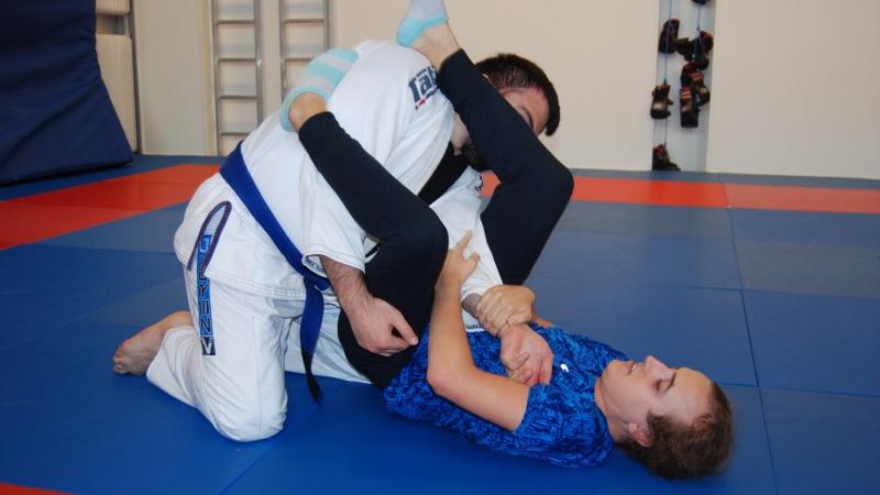 Två träningsklädda ungdomar i brottargrepp på en mjuk matta på golvet.