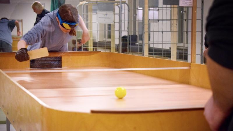 En spelare med ögonbindel håller i en racket och lutar sig fram över showdownbordet med ramp.