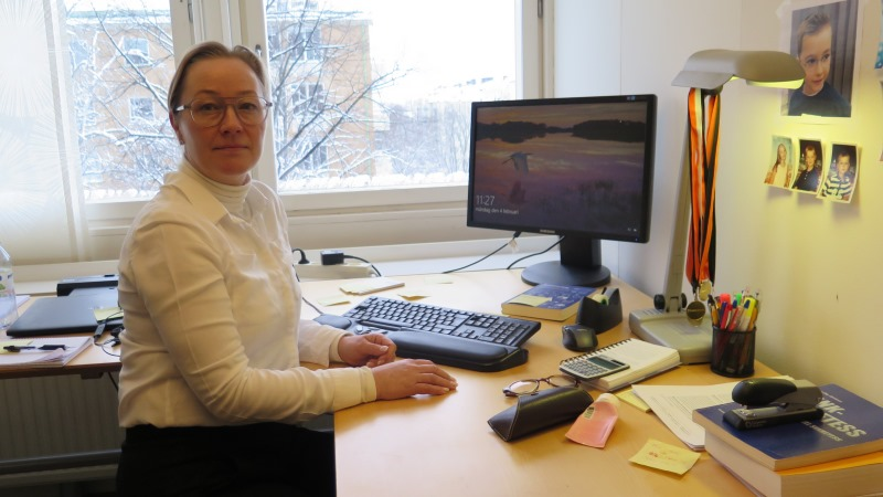 En blond kvinna i vit blus och glasögon sitter vid ett skrivbord.