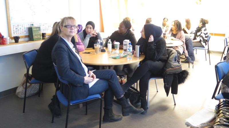 Läraren Cecilia Lindeberg vid ett runt bord i ett klassrum. I bakgrunden studenter inbegripna i livligt samtal.