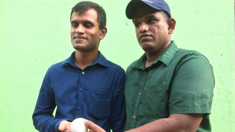 En man i blå skjorta och en man i grön skjorta och blå keps håller tillsammans i en liten vit boll framför en ljusgrön bakgrund.