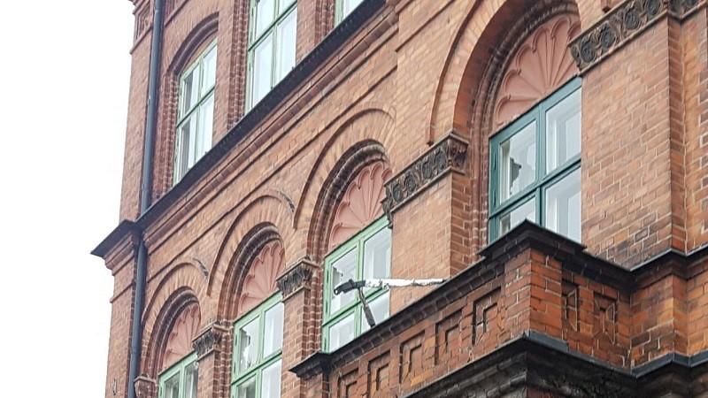 En tegelfasad till ett hus med välvda fönsterbågar och en balkong. Kontoret för Nationellt kunskapcentrum för dövblindfrågor.