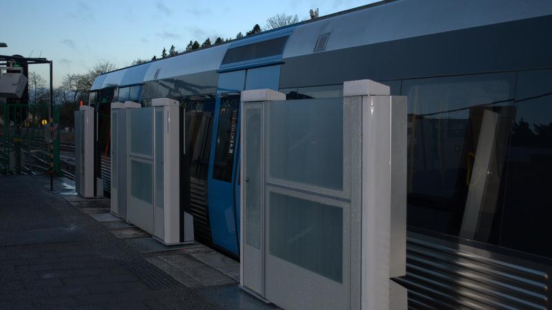 Plattformsdörrar i glas som öppnas för ett tåg.