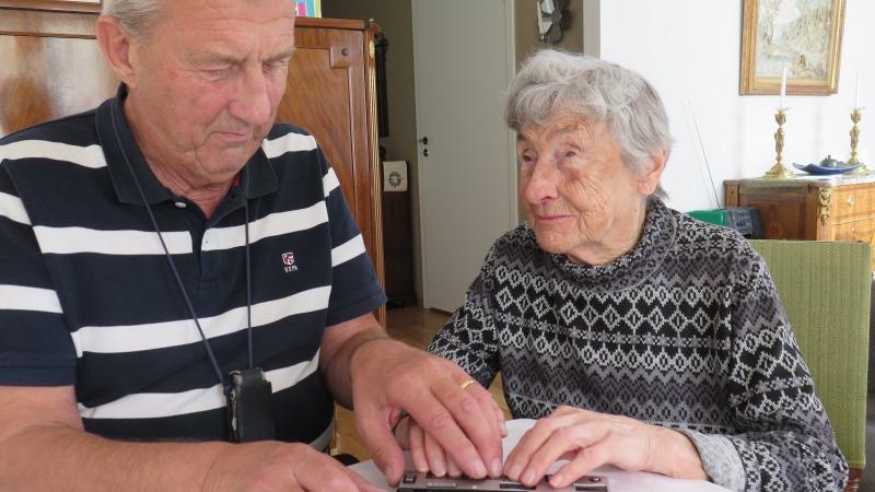 Kjell Börjesson och Dagny Georgii med händerna på punktdisplay. Dagny har kort gråvitt hår och mönstrad gråvit tröja.